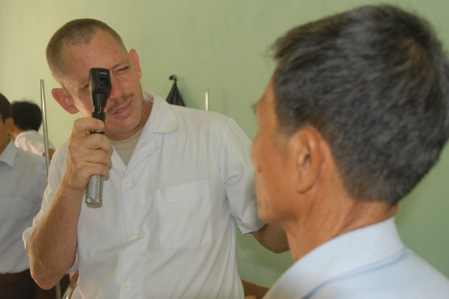 Maj. Daniel Gruver, an Optometrist from Schofield Barracks, Hawaii, conducts an eye examination for a local resident of the Bac Ninh Province of Vietnam, July 11.