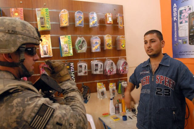 1st Lt. Daniel Braud, a Kingwood, Texas native, and platoon leader in 4th Squadron, 9th Cavalry Regiment, 2nd Brigade Combat Team, 1st Cavalry Division, checks on a cell phone store in Daquq, Iraq, July 7, which is owned by Ali Abbas Muhsin, who used a U.S.-issued micro-grant to revitalize his business.