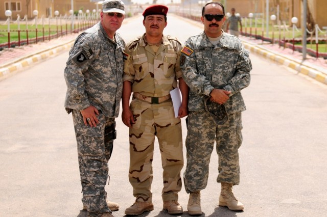 """MAHMUDIYAH - Sgt. Waine Haley, of 30th Heavy Brigade Combat Team, (left) poses with Sgt. Saad Salim Khashan, of the 17th Iraqi Division and an interpreter known as """"John,"""" as an Iraqi public affairs student practiced camera techniques during a class Haley taught at the compound here June 22. Haley taught basic camera techniques to four Iraqi Soldiers and assessed broadcasting equipment during the five-day class."""