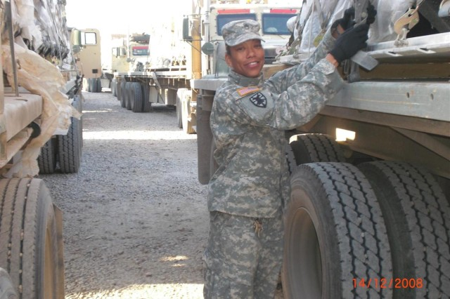Staff Sgt. Carlenna Hawkins, a squad leader with the 70th Transportation Company, double checks the tie-down straps of equipment on a tractor-trailer prior to a mission at Contingency Operating Base Speicher, Iraq in Dec. 2008.