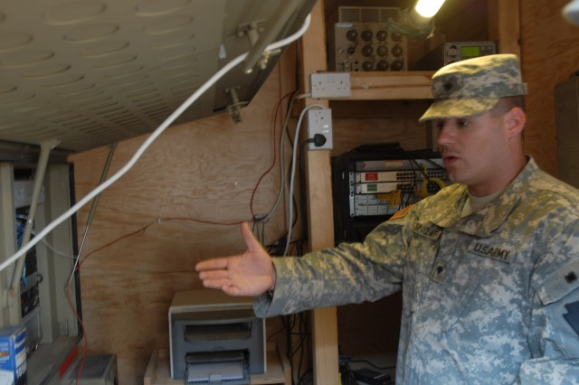 CAMP TAJI, Iraq - Spc. Robert Sinclair of Indiana, Pa., a satellite technician with 656th Signal Company, 56th Stryker Brigade Combat Team,explains the importance of a satellite transmission terminal July 10. The terminal enables Soldiers to make phone calls utilizing a satellite 22,000 miles above earth.
