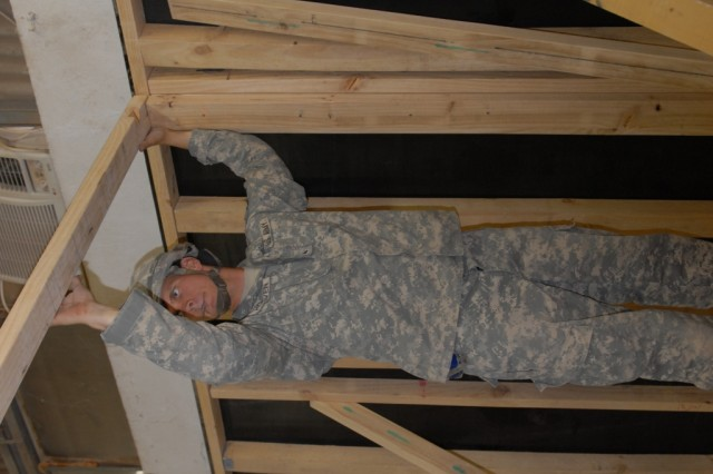 """BAGHDAD -Cpl. Nathan Hoover, Carpenter, 46th Engineer Combat Battalion (Heavy), a native of Lilly, PA sets up a partition wall while helping to build housing units for Soldiers moving to Forward Operating Base Shield July 11. MND-B engineer Soldiers are turning an old hanger into a housing complex of 50 double-stacked rooms. """"I like working on a project from scratch, said Hoover. """"It's pretty special especially for the incoming Soldiers."""" The project is expected to be completed by mid August."""