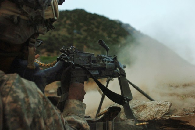 A U.S. Army Soldier with 1st Battalion, 32nd Infantry Regiment, 10th Mountain Division, fires at anti-Afghanistan forces attacking from the hills surrounding the remote village of Barge Matal during Operation Mountain Fire in Afghanistan's Nuristan province, July 12. During the operation, U.S. and Afghan national security forces quickly secured the tiny mountain village, which was overwhelmed by AAF several days prior. (Photo by U.S. Army Sgt. Matthew C. Moeller, 5th Mobile Public Affairs Detachment)