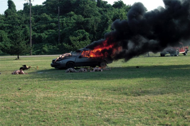 A car used to simulate a terrorist attack with a Vehicle-borne Improvised Explosive Device burns on Story's Chapel Field. Fire and Emergency Services, Emergency Management and installation law enforcement participated in the mass casualty exercise. This year's event is the first time the two military installations have conducted the exercise as a joint base effort.