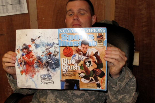 """BAGHDAD -  Oxford, N.C. native, Maj. Robert """"Bert"""" Kemp III relaxes while reading his Sports Illustrated magazine commemorating the University of North Carolina - Chapel Hill's NCAA Basketball Tournament victory in his office at Forward Operating Base Falcon, Iraq, south of Baghdad.  The 1993 Chapel Hill graduate is serving in Iraq with the North Carolina National Guard's 30th Heavy Brigade Combat Team.  Kemp earned his law degree from Wake Forest University."""