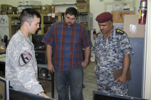 Capt. Mike Silverman, battalion intelligence officer for 3rd Battalion, 8th Cavalry Regiment, shows an Iraqi Security Force liaison officer mission essential information in the 3rd Battalion, 8th Cavalry Regiment tactical operations center.