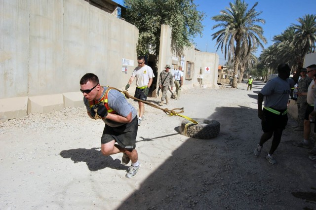 """BAGHDAD - Killeen, Texas native 2nd Lt. Brent Beadle drags a 75-pound humvee tire 100 yards during the """"Black Knight"""" 1000 Competition at Joint Security Station Shield, east of Baghdad, July 12.  The 1st """"Black Knight"""" Battalion, 5th Cavalry Regiment, attached to the 1st Brigade Combat Team, 1st Cavalry Division held this seven-event partner relay to test the endurance and stamina of the Soldiers."""