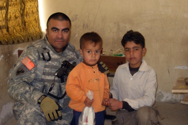 "BAGHDAD - Staff Sgt. Dionisio ""Danny"" Alcala, a civil affairs Soldier assigned to the 425th Civil Affairs Battalion, 364th Civil Affairs Brigade, 1st Cavalry Division, makes new friends while on a mission. The Los Angeles native left his family's real estate business to join the Santa Barbara-based 425th CA Bn. Alcala said he enjoys his job so much, he plans to extend his deployment and volunteer for a future deployment to Afghanistan."
