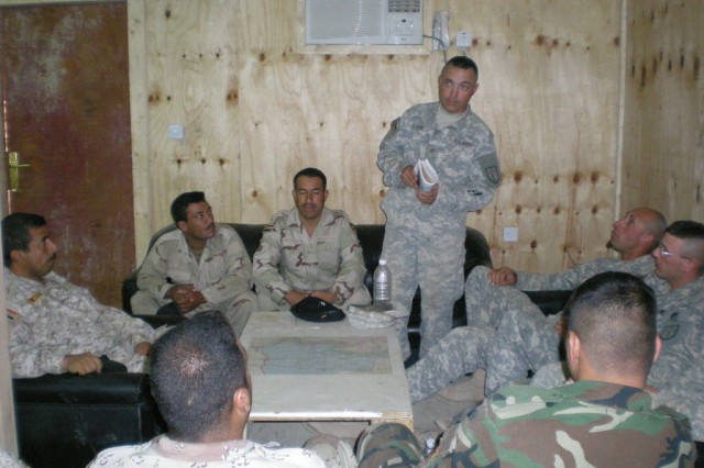 BAGHDAD - Sgt. Heith Kafer, carpentery/masonry specialist, 46th Engineer Combat Battalion (Heavy), 225th Engineer Brigade, of Medford, Ore., briefs construction safety tips to Iraqi and U.S. Soldiers. The 6th Iraqi Army Engineer Regiment Soldiers are receiving training to help build five Army B-huts and safety platforms in five guard towers at Joint Security Station Tarmiyah.