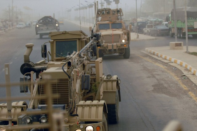 TAJI, Iraq - Two Mine Resistant Ambush Protected vehicles move along a highway in the vicinity of Taji Market, north of Baghdad, July 13, followed by an engineer-variant Stryker vehicle. Soldiers of 856th Engineer Company, 56th Stryker Brigade Combat Team, used the vehicles during an hours-long route clearance mission.