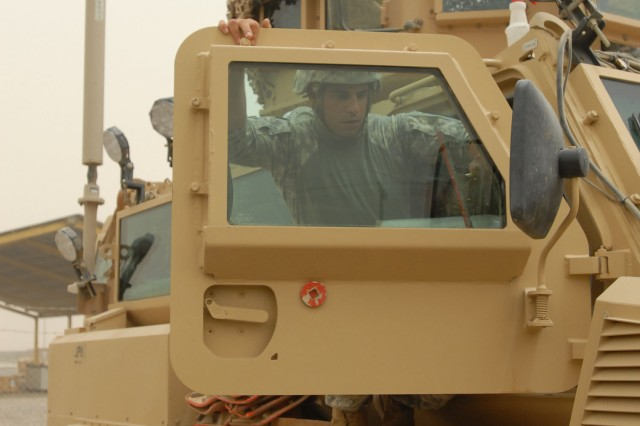 TAJI, Iraq -Pvt. Alfred Dorsey of Philadelphia cleans the window of an MRAP vehicle door on Camp Taji, Iraq, a base camp north of Baghdad, July 13 prior to a route clearance mission while Sgt. Ryan Bednarski of Portgage, Pa. loads a .50 caliber machine gun. Both Soldiers are with 2nd Platoon, 856th Engineer Company, 56th Stryker Brigade Combat Team.