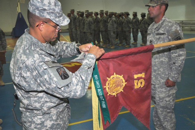 Col. Martin B. Pitts, commander, 16th Sustainment Brigade, ties a green safety streamer to the guidon of 51st Transportation Company, 30th Combat Sustainment Support Battalion, 16th Sust. Bde., during a ceremony at the Morale, Welfare and Recreation base complex at Contingency Operating Base Q-West, Iraq June 30. It was the second safety streamer awarded to the Mannheim, Germany-based Soldiers of the 51st Trans. Co. The transportation Soldiers assumed authority July 12, 2008, and are on a 15-month deployment.