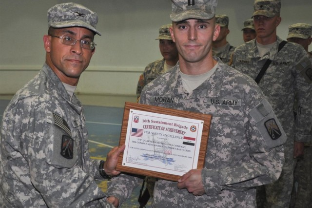 Col. Martin B. Pitts, commander, 16th Sustainment Brigade, presents Capt. Paul Moran, 574th Quartermaster Company, 30th Combat Sustainment Support Battalion, 16th Sust. Bde., with a certificate of appreciation for going 90 days without an accident, during a ceremony at the Morale, Welfare and Recreation base complex at Contingency Operating Base Q-West, Iraq, June 30. Pitts also awarded a green safety streamer to the 574th QM Co., a Grafenwoehr, Germany based unit and on a 15-month deployment since July 26, 2008.