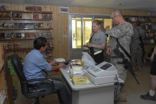 Soldiers make purchases from an Iraqi owned business at the UR market at Contigency Base Adder, Iraq June 19