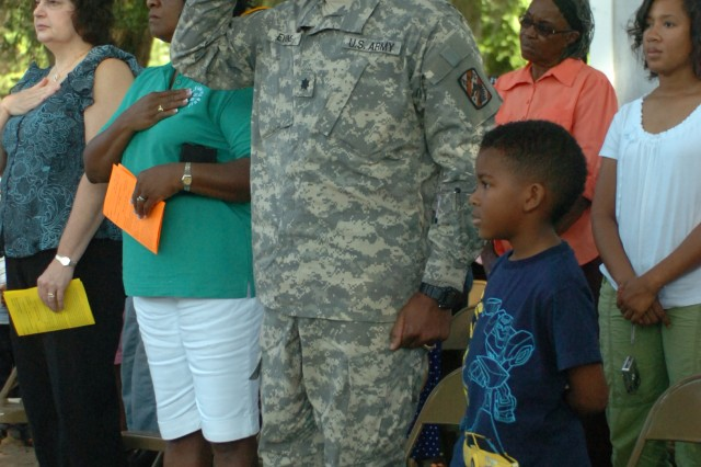 Lieutenat Colonel Lillard Evans, commander of the 260th Quartermaster Bn., 3rd Sustainment Bde., salutes the flag at the 11th Annual Project Reach GANG Back to School Rally, July 11.