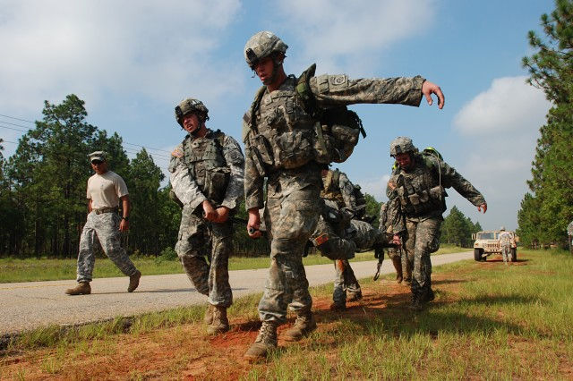 """Spc. Stephen Segars (left) and Pfc. Colby Mooney (right) of Mortars Platoon, Headquarters Troop, 1st Squadron, 73rd Cavalry Regiment, 2nd Brigade Combat Team, 82nd Airborne Division, litter carry a teammate during the 1-73 Cav's """"Stress Shoot"""" competition at Fort Bragg, NC July 15. The event put the competitors through a grueling series of physical challenges culminating in a marksmanship competition to see who could shoot the best under the most stressful conditions. (U.S. Army photo by SSG Mike Pryor, 2nd BCT, 82nd Abn Div PAO)"""