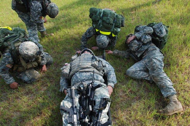 """Paratroopers from Mortars Platoon, Headquarters Troop, 1st Squadron, 73rd Cavalry Regiment, 2nd Brigade Combat Team, 82nd Airborne Division, drop to the ground from exhaustion while litter carrying a plus-sized teammate during the 1-73 Cav's """"Stress Shoot"""" competition at Fort Bragg, NC July 15. The event put the competitiors through a grueling series of physical challenges culminating in a marksmanship competition to see who could shoot the best under the most stressful conditions. (U.S. Army photo by SSG Mike Pryor, 2nd BCT, 82nd Abn Div PAO)"""