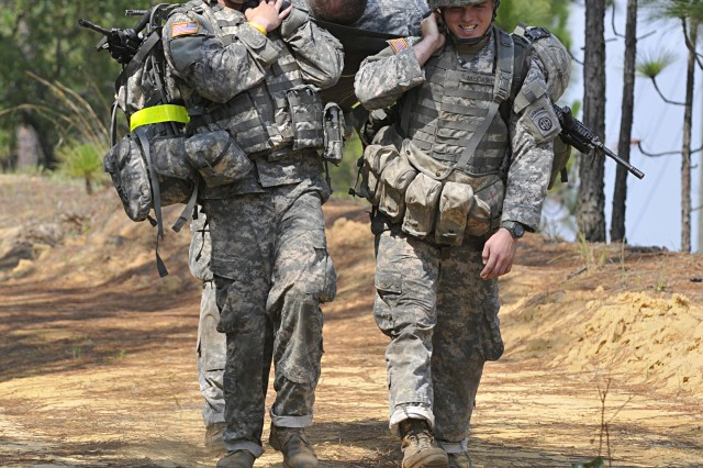 "Pvt. Shawn Griffith (left) and Sgt. Michael McCaskey, of A Troop, 1st Squadron, 73rd Cavalry Regiment, 2nd Brigade Combat Team, 82nd Airborne Division, help carry Pfc. Scott Vest 500 meters on a litter during the 1-73 Cav's ""Stress Shoot"" competition at Fort Bragg, NC July 15. The event put the competitiors through a grueling series of physical challenges culminating in a marksmanship competition to see who could be the best shot under the most stressful conditions. (U.S. Army photo by Pfc. Kissta Feldner, 2nd BCT, 82nd Abn Div PAO)"