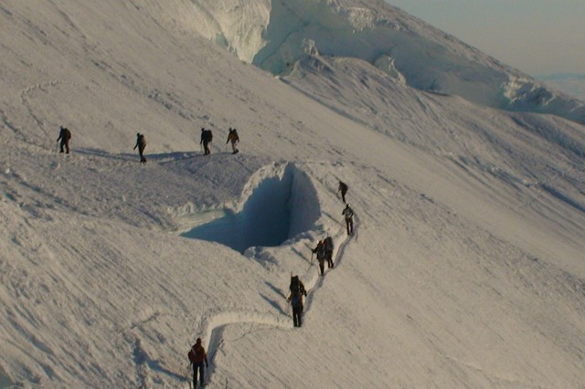 Members of Camp Patriot and the supporting crew cross a crevasse on the Emmons Glacier during a climb to the summit of Mt. Rainier July 9, 2009.  Camp Patriot is a non-profit organization that helps injured veterans enjoy outdoor activities.