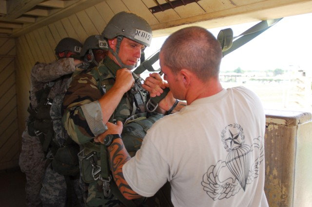 Securing static line to harness.jpg: SSG William Wallace, Black Hat instructor with 4th Platoon, B Company, secures a static line to the harness of Petty Officer 1st Class Richard Hubez-Chartraw.