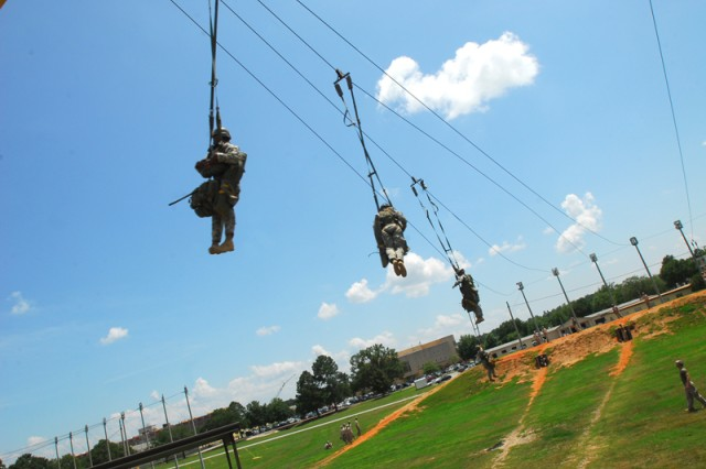 Across the landing area.jpg: A squad is carried along the cable toward the landing area, where Soldiers wait to assist them off the cable. As they swing across the field, the squad releases packs full of mission equipment.