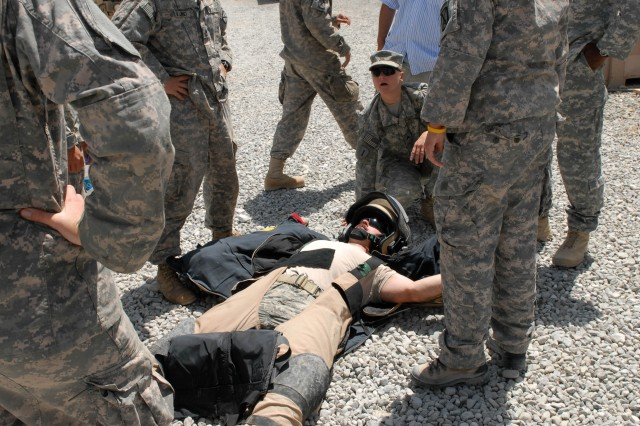 "U.S Army Sgt. Christine Hein demonstrates how to remove a bomb suit from Air Force Tech Sgt. Brandon L. Livingston during training at Forward Operating Base Shank, July 17. The combined Counter Improvised Explosive Device team with 3rd Brigade, 10th Mountain Division, ""treated"" their casualty for exhaustion and dehydration which are possible during real missions in the 80 lb. suit. (Photo by U.S. Army Spc. Matthew Thompson, 5th Mobile Public Affairs Detachment)"