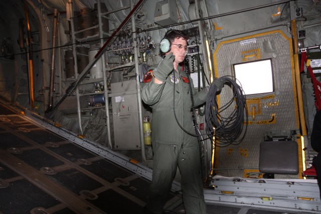 Master Sgt., Brent Simpson, Loadmaster, prepares to plug in the commo cord for the flight crew in preparation for the Black Dagger Drop.