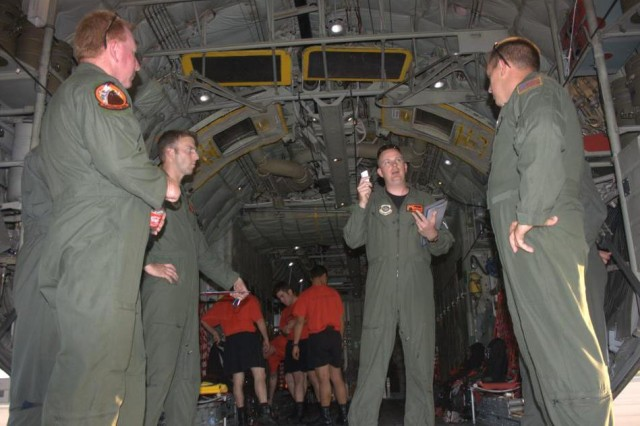 Aircraft Commander, Capt. Robert Dodson, gives his pilot brief to the flight crew aboard the C130H before the Black Dagger drop. Master Sgt. Matt Stone, Flight Engineer and 1st. Lt. Jeff Hilsenbeck, Navigator are pictured left to right and Staff Sgt. Justin Kass, Loadmaster, on the right.