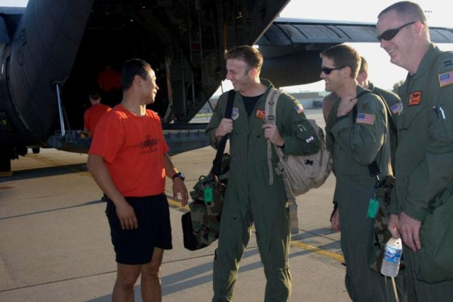 Lt. Jeff Hilsenbeck, Navigator, Maj. Jeff Herrmann, Co-pilot and Capt. Robert Dodson, Air Craft Commander, talk to USASOC Black Dagger, Staff Sgt. Dewey Vinaya, before they board the C130H for the paratrooper drop.