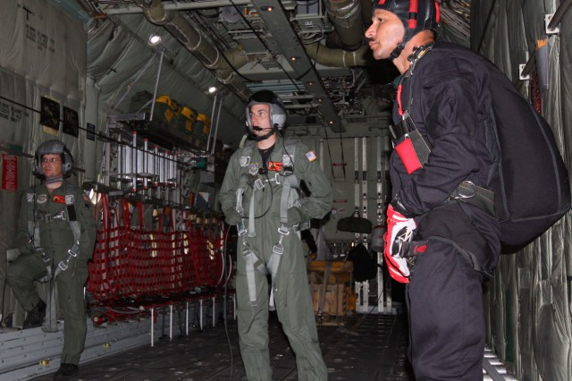 Loadmasters, Master Sgt., Brent Simpson and Senior Airman, Brad Emmett in flight with USASOC Black Dagger, Sgt. Maj. Abe Sanchez on the C130H aircraft.