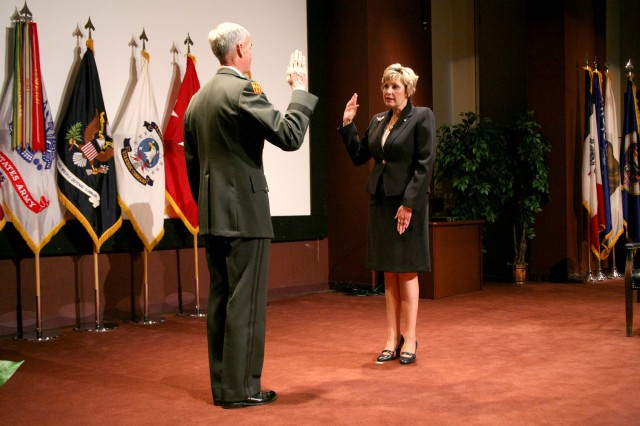 """Lt. Gen. Kevin Campbell, commanding general, U.S. Army Space and Missile Defense Command/Army Forces Strategic Command, administers the oath of office to Mary """"Cathy"""" Dickens during her Senior Executive Service promotion ceremony July 10 at Bob Jones Auditorium. Dickens was selected in June as the Prinicpal Assistant Responsible for Contracting/Director, Contracting and Acquisition Management Office."""
