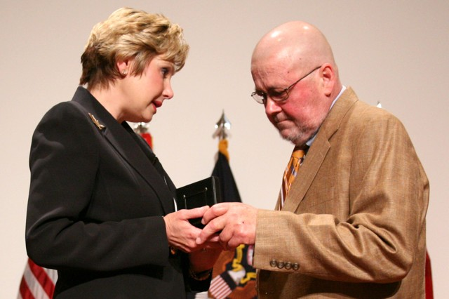 """Mary """"Cathy"""" Dickens presents her husband, Winston, a watch during Dickens' Senior Executive Service promotion ceremony July 10 at Bob Jones Auditorium. Dickens was selected in June as the Prinicpal Assistant Responsible for Contracting/Director, Contracting and Acquisition Management Office at the U.S. Army Space and Missile Defense Command/Army Forces Strategic Command."""