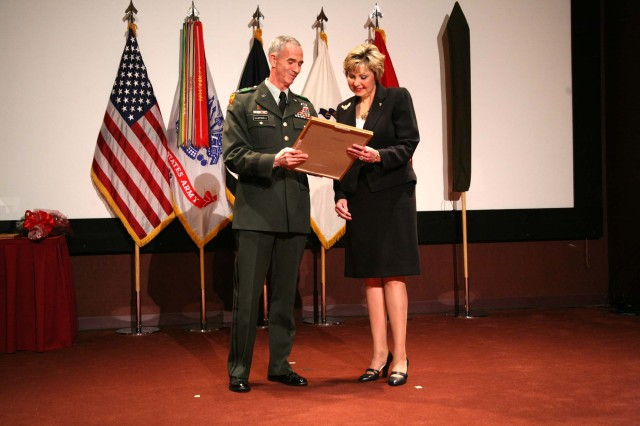 """Lt. Gen. Kevin Campbell, command general, U.S. Army Space and Missile Defense Command/Army Forces Strategic Command, presents Mary """"Cathy"""" Dickens an award during Dickens' Senior Executive Service promotion ceremony July 10 at Bob Jones Auditorium. Dickens was selected as the Principal Assistant Responsible for Contracting/Director, Contracting and Acquisition Management Office at USASMDC/ARSTRAT in June."""