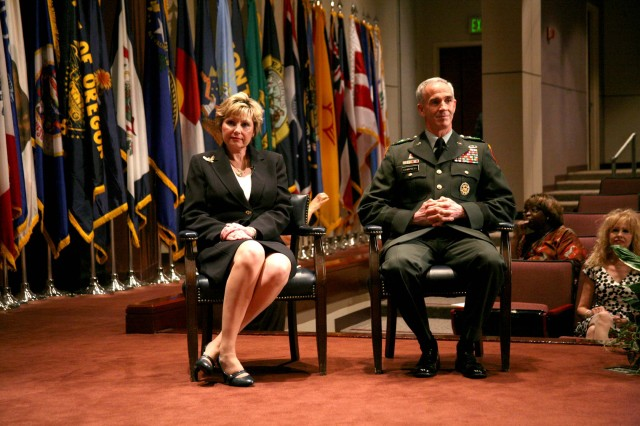 """Mary """"Cathy"""" Dickens, Principal Assistant Responsible for Contracting/Director, Contracting and Acquisition Management Office, and Lt. Gen. Kevin Campbell, commanding general, U.S. Army Space and Missile Defense Command/Army Forces Strategic Command, listen to the narrator during Dickens' Senior Executive Service promotion ceremony July 10."""