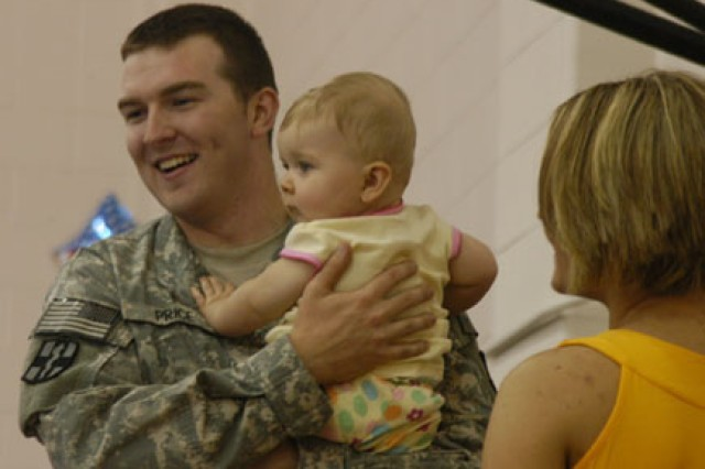 FORT POLK, La. -- Spc. James Price is reunited with his 7-month-old daughter, Holly Alexis, and his wife Jennifer, at the 115th Combat Support Hospital's advon redeployment at the 1st Maneuver Enhancement Brigade gym July 9.