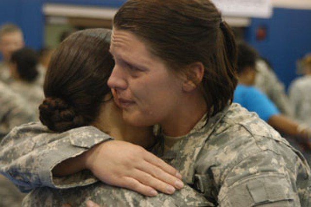 Spc. Danielle Quintero (left) and Sgt. Nikki Bosarge hug after the 115th Combat Support Hospital's advon redeployment July 9. 115th CSH Soldiers have been deployed to Iraq for 15 months.
