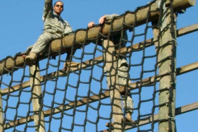 Staff Sgt. Noel Espinal, Headquarters and Headquarters Battery, 5th Bn, 25th FA, 4th BCT, 10th Mtn Div, waves from atop an obstacle at Fort Polk's obstacle course July 1.