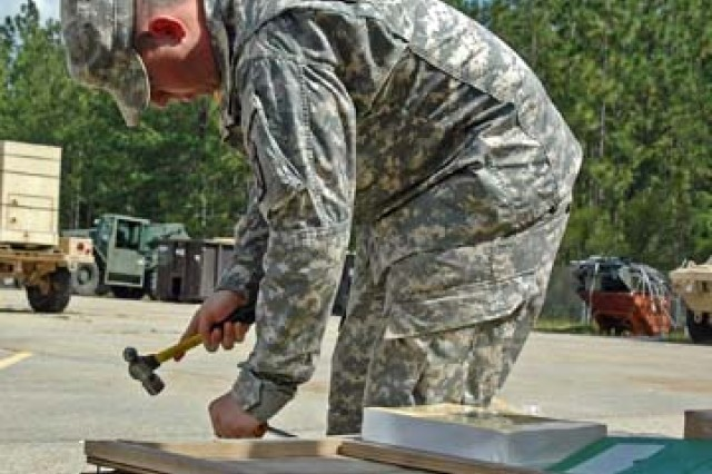 Spc. Derek Nitcholas, FSC E, 94th BSB, 4th BCT, 10th Mtn Div opens a box of basic issue items for FMTV trucks equipped with LTAS upgrades.