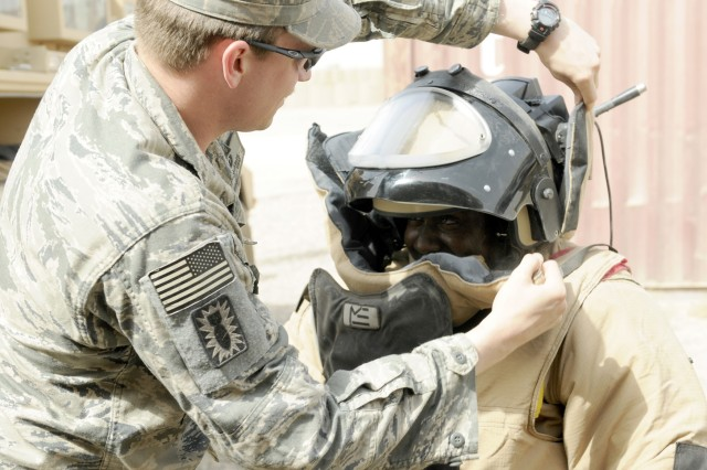 ZAIDAN, Iraq - Tech Sgt. Matthew Stark, with the 447th Explosive Ordnance Disposal team, (left) helps Sgt. Mica Joseph, with 1st Battalion, 113th Field Artillery Regiment, 30th Heavy Brigade Combat Team, put on the bomb suit worn by EOD when they have to approach an explosive device. Stark, of Buffalo, N.Y., recently spent the afternoon at Combat Outpost Meade, showing soldiers the equipment used by the EOD team.