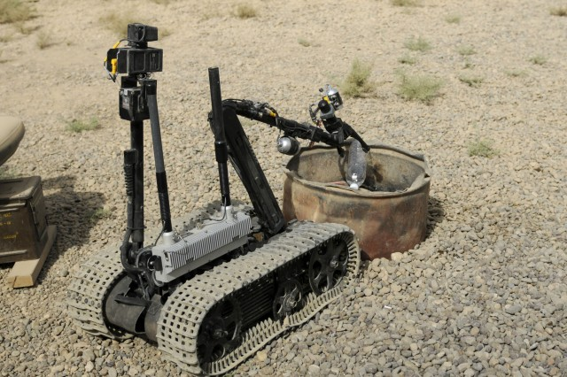 ZAIDAN, Iraq - A remote-controlled robot used by the explosive ordnance team at Combat Outpost Meade, puts a bottle of water in a barrel, showing its abilities. Airman 1st Class Hans Metz with the 447th Explosive Ordnance Disposal team, controlled the device.