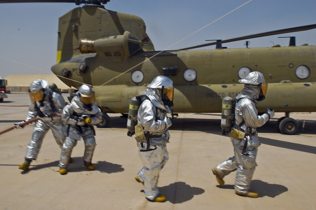 TAJI, Iraq- Fully suited firefighters from the Taji fire department move quickly to shut down vital systems on a CH-47F Chinook helicopter so they can battle a mock fire, July 17,  at Camp Taji, Iraq.  This was part of a training exercise held by 2nd Battalion, 227th Aviation Regiment, 1st Air Cavalry Brigade, 1st Cavalry Division, Multi-National Division - Baghdad, designed to test the firefighters familiarization with the aircraft in the event of an actual fire.
