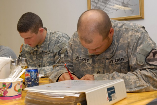 BAGHDAD - Spc. Andrew Lemons (left), an imagery analyst with Company B, Division Special Troops Battalion, 1st Cavalry Division, Multi-National Division-Baghdad, from Houston, and Spc. Cory Elliott, a wheeled vehicle mechanic with Headquarters Service Company, DSTB, 1st Cav. Div. from Dekalb, Ill., work on a customary units of measure quiz to start off the day's class here July 16. Each class begins with a quiz that reviews the homework assignment from the night before.