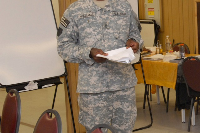 """BAGHDAD - Sgt. 1st Class Valroy Williams, an operations noncomissioned officer with the 18th Fires Brigade attached to Company A, Division Special Troops Battalion, 1st Cavalry Division, reviews the answers to the English portion of the final assessment test for the class, July 17. This class cycle is the tenth for Williams, who is from Trinidad, West Indies. """"I've seen immediate results with students who put in warrant officer packets and officer packets within weeks, some who have received special assignments and others who have changed their MOS within days after achieving a GT (general technical) score of 110 or higher,"""" he said."""