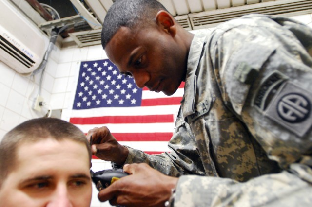 Sgt. Teo Garcia prepares to cut a Soldier's hair July 20, at Joint Security Station Loyalty, Iraq, located in the 9 Nissan district of eastern Baghdad. Garcia says cutting hair relaxes him even during the most stressful of times during his deployment to Iraq.