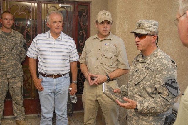 TAJI, Iraq- Nevada Gov. Jim Gibbons (left) and Texas Gov. Rick Perry (center), listen as Lt. Col. Ralph Litscher (right), from Half Moon Bay, Calif., commander of 2nd Battalion, 227th Aviation Regiment, 1st Air Cavalry Brigade, 1st Cavalry Division, Multi-National Division - Baghdad, explains medevac procedures, July 18, at Camp Taji, Iraq, as part of the governors visit to the 1st ACB. The governors from Illinois, Missouri and Minnesota were also present during the visit.