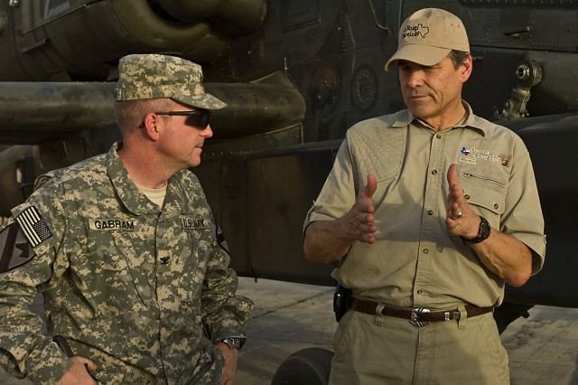 "TAJI, Iraq- While standing in front of an AH-64D Apache attack helicopter, Texas Gov. Rick Perry (right) discusses weapons systems with Col. Douglas Gabram of Cleveland, Ohio, commander of the 1st Air Cavalry Brigade, 1st Cavalry Division, Multi-National Division - Baghdad, during a visit to Camp Taji, Iraq, July 18. Perry, along with govenors from Illinois, Minnesota, Nevada and Missouri also visited the troopers of the 1st ACB. ""I've seen the Cav. back home at (Fort) Hood but never in Iraq,"" Perry said. ""It was nice to touch hands, touch hearts and touch minds."""