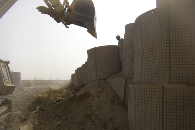 BAGHDAD - Staff Sgt. Mario Haywood (on top of the barriers), a native of Anchorage, Alaska, squad leader, 46th Engineer Combat Battalion (Heavy), 225th Engineer Brigade, ground guides Whitewater, Mo. native, Spc. David Burke, heavy equipment operator, 46th ECB (H), as he demolishes existing HESCO barriers and an earth berm wall, July 19 at Task Force Raptor here, with a hydraulic excavator to reconstruct the HESCO walls that separated four ranges.