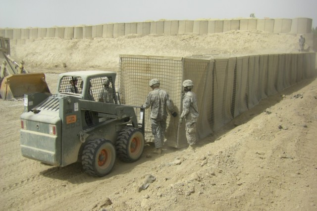 BAGHDAD - Soldiers of earthmoving platoon, 46th Engineer Combat Battalion (Heavy), 225th Engineer Brigade, use a Bobcat loader to set up HESCO barriers, large containers filled with dirt used for force protection, during their range construction project July 19 at Task Force Raptor here.