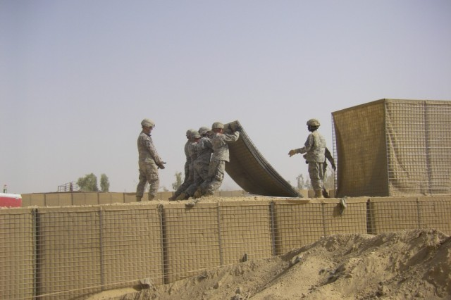 BAGHDAD - Soldiers of Company B, 46th Engineer Combat Battalion (Heavy), 225th Engineer Brigade, lift an empty HESCO barrier into place to create the second tier of the range separation wall July 19 at Task Force Raptor here.  The wall will protect Soldiers from ricochets and allow the range to be used for a wider range of training activities.