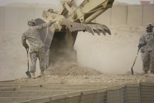 BAGHDAD - Pvt. Gary McFadden of London, Ky., heavy equipment operator,  46th Engineer Combat Battalion (Heavy), 225th Engineer Brigade, ground guides  the hydraulic excavator operator driven by Spc. Mark Dillon of Reed City, Mich., as he fills HESCO barriers with sand and dirt at Task Force Raptor here. Soldiers use shovels to even out the dirt fill in the baskets.